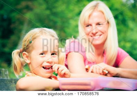 family having a picnic, enjoyng a nice summer day outdoors.