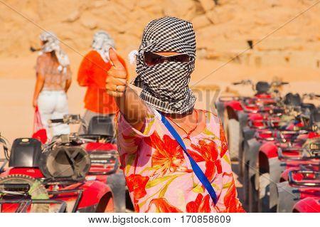 SHARM EL SHEIKH EGYPT - JULY 9 2009. Caucasian girl in head kerchief in the desert.