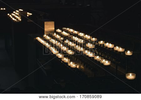 Germany, Cologne- March, 2016 A lot of burning candles in candlesticks are in the cathedral