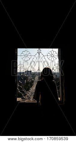 Silhouette girl who looking view of Vientiane thru the Buddha image window at Patuxay Vientiane
