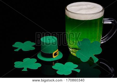 Glass mug of green beer with a decorative shamrocks  on a black background. St Patrick's Day.