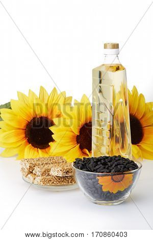 Sunflowers, seed, vegetable oil in a bottle and sweetness from pressed sunflower seeds candied in sweet syrup (sunflower seed brittle) on a white background. Sweet dessert. Harvest.