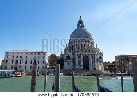 Venice cityscape view on Santa Maria della Salute basilica with gondolas on the Grand canal in Venice