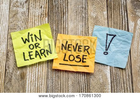 Win or learn, never loose - reminder on sticky notes against a grunge wood