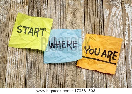 Start where you are advice - handwriting on sticky notes against grunge wood