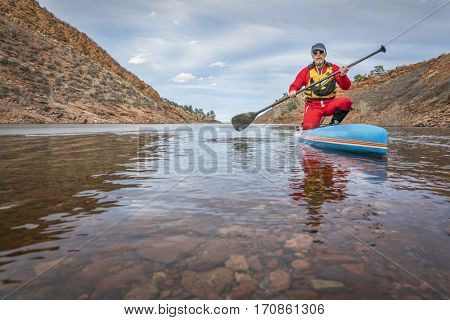 senior male paddler in drysuit  is enjoying stand up paddling on lake in Colorado, winter scenery with some ice