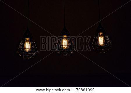 Three hanging lights in the dark contrast