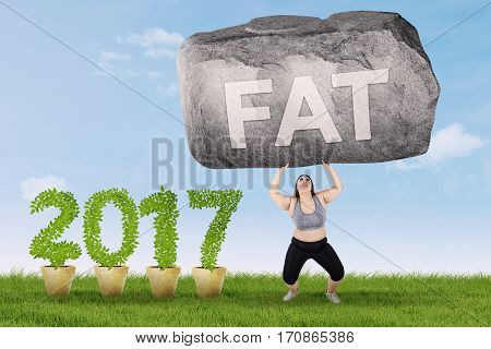 Overweight young woman wearing sportswear and lifting a big stone with fat text near number 2017 shot outdoors