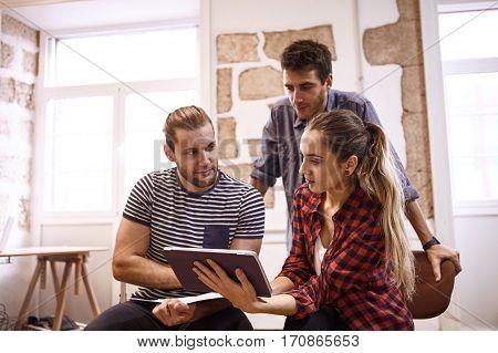 Three Young Creatives Looking At Tablet