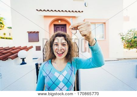 Woman With Keys Standing Outside New Home.
