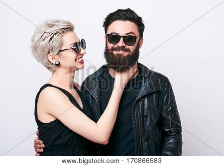 Couple having a funny argument. Fashion young woman and bearded man trying to kill each other while smiling. Sick of relationship concept