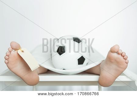 Boy Lying On A Mortuary Slab With A Soccer Ball