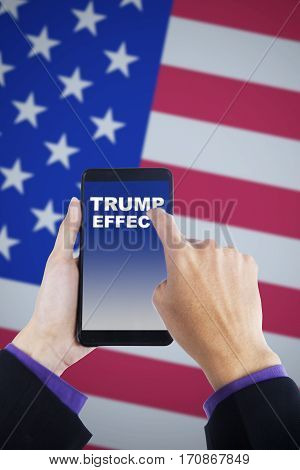 Close up of worker hands touching word on the Trump Effect on the mobile phone with United States flag in the background