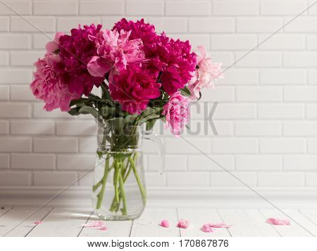 Beautiful bouquet of pink peonies in glass vase on the white brick and wood background.