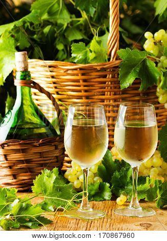 Two glasses and bottle of white wine basket of grapes. wooden background