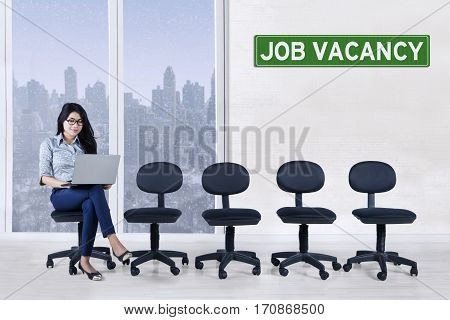 Young woman using a laptop while sitting on a chair with text of job vacancy on a signboard and empty chairs in the office
