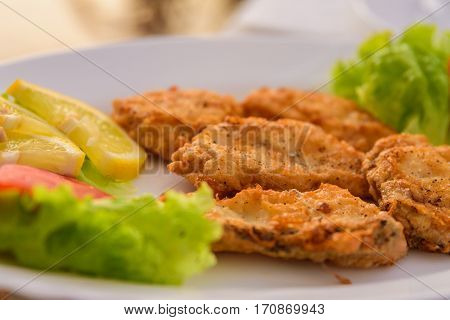 Fried fish in batter. Very tasty food on a light background.
