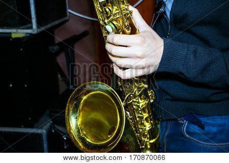 Man plays a tenor sax Golden color