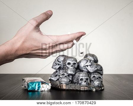 Male hand holding cigarette skulls on the table Anti smoking concept
