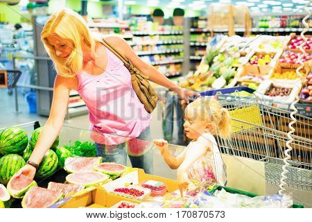 mother and daughter buying groceries at the supermarket
