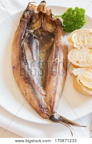 Manx Kippers or skeddan jiarg naturally smoked herrings produced in the Isle of Man with melted butter and bread rolls