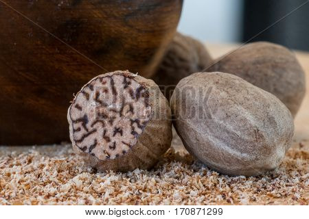 Close Up of Whole Nutmeg and Ground Nutmeg on butcher block