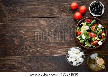 Bowl of fresh salad with feta for healthy eating on wooden table. Top view copy space.