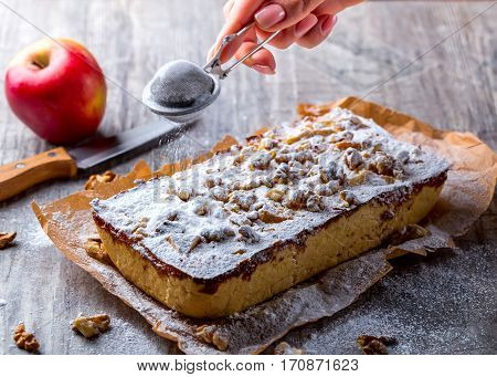 Apple pie dusted with powdered sugar on a grey background. Hand sprinkle the tart with powdered sugar. Red Apple is in the background. Selective focus