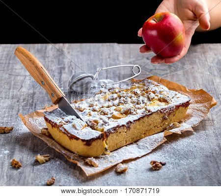 Apple pie dusted with powdered sugar on a grey background. The knife stuck into the tart. Red Apple in hand. Selective focus