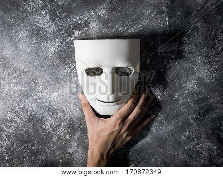 Hand holding white mask on gray grunge background.