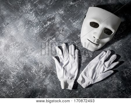 White mask with glove on gray grunge background.
