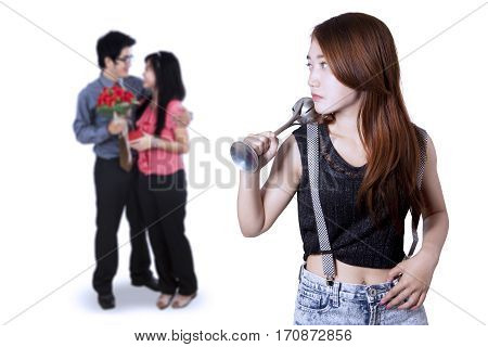 Teenage girl jealous to romantic young couple while holding a beater tool isolated on white background