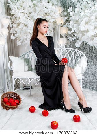 Lady In Black Dress Sitting In A Snow Covered Park