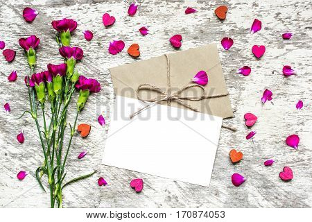 blank white greeting card and envelope with purple carnation flowers and wooden hearts over white rustic table. mock up. valentines day background