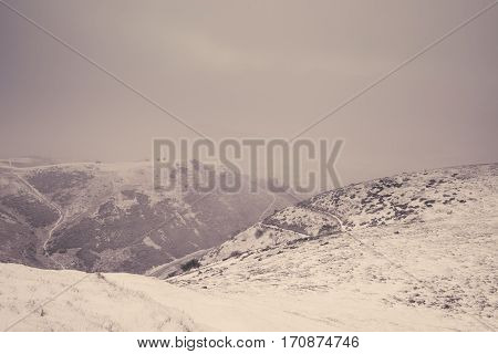 Snow Covered Hills In Mist Caused by Blizzard