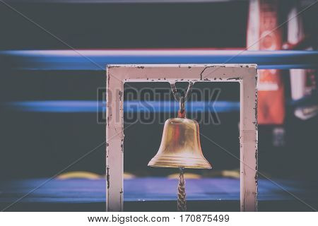 Brass Boxing Bell Suspended on Metal Frame With Blurry Fighting Ring in Background