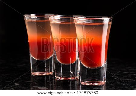 row of bloody Mary shots on marble table