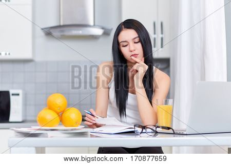 Portrait of pretty girl in glasses thinking about exercise of home task. Woman using lap top and reading book. Touching chin by hand. Stylish interior of kitchen with juice and oranges on table.