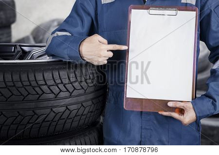 Close up of mechanic pointing to blank paper on the clipboard while standing besides stack of tyre