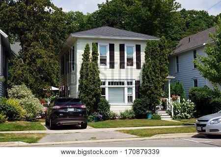 HARBOR SPRINGS, MICHIGAN / UNITED STATES - AUGUST 4, 2016: A single-family home behind tall, sculpted arborvitae bushes (Thuja occidentalis), on West Third Streets in Harbor Springs.