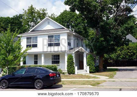 HARBOR SPRINGS, MICHIGAN / UNITED STATES - AUGUST 4, 2016: A white, single-family home with a wraparound porch on West Third Streets in Harbor Springs.