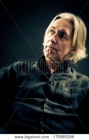senior man's portrait, taken in studio on black background