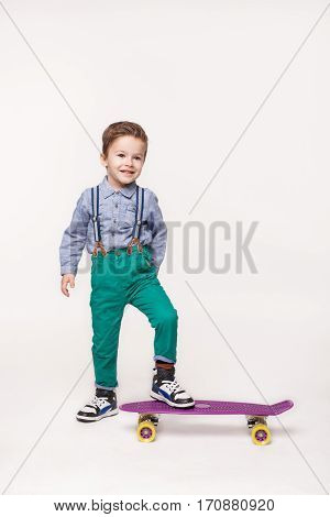 Young skater isolated on white. Little boy wearing stylish clothes standing on skateboard