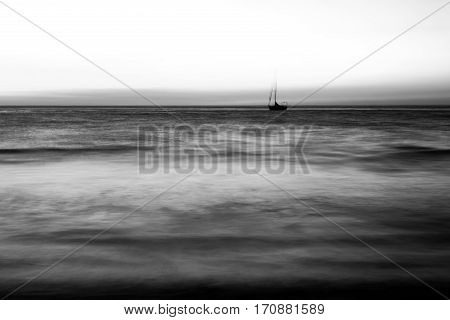 Black and white image of a lone ship in the ocean.