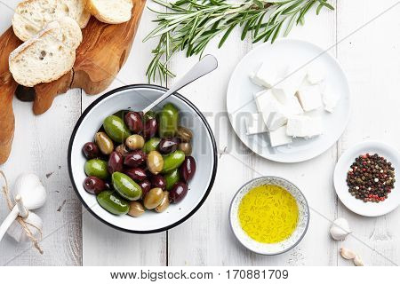 Ciabatta bread, fresh olives, feta cheese, rosemary twigs, garlic, peppercorns and olive oil on white wooden background