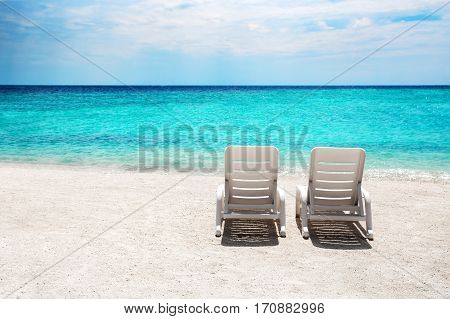 Two sun beds on white sand beach at tropical island