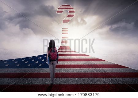 Image of female student carrying a backpack and book while walking on the highway with USA flag and a question mark