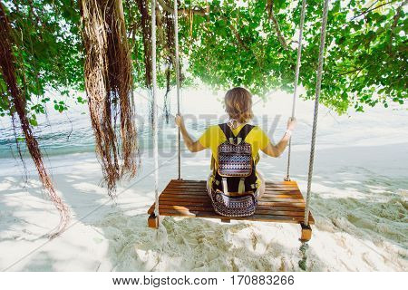 Woman on swing at tropical sand beach island