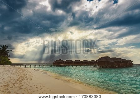 Heaven sun rays over water bungalows at tropical island resort