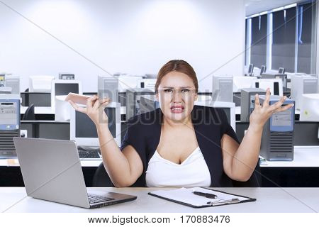 Portrait of female entrepreneur confused with her job while shrugs her shoulder in the office